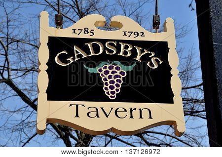 Alexandria Virginia - April 13 2014: Sign painted with a bunch of grapes hangs in front of historic 18th century Gadsby's Tavern