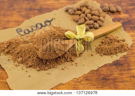 Cacao Powder, Wooden Spoon And Candy On Cooking Paper