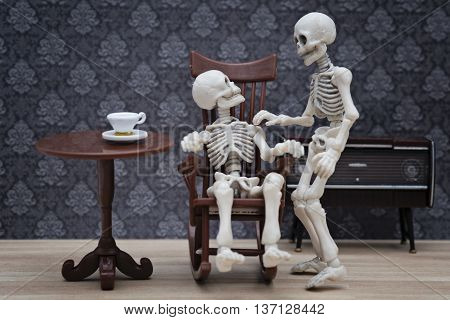 A skeleton talking with other skeleton sitting on rocking chair