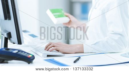 Pharmacist holding a medicine packet and searching that product in the computer database healthcare and technology concept