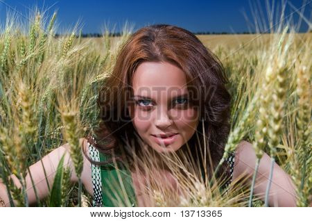 beautiful woman sitting on wheat field