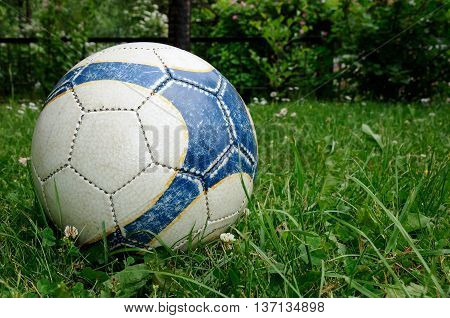 old soccer ball in the green grass on the lawn
