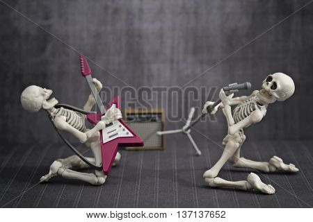 Two skeletons band playing rock music in a grungy room