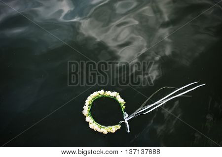 Wreath with white roses and ribbon on wather