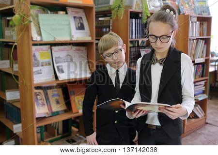 pupil in black jacket and sunglasses and schoolgirl,holding book, read it on background of shelves with books