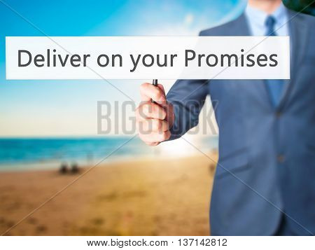 Deliver On Your Promises - Businessman Hand Holding Sign