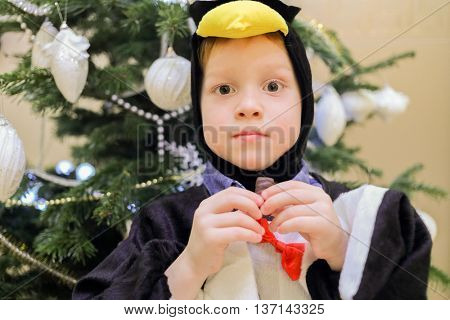 Half-length portrait of boy dressed as penguin and looking at us, standing near Christmas tree in living room