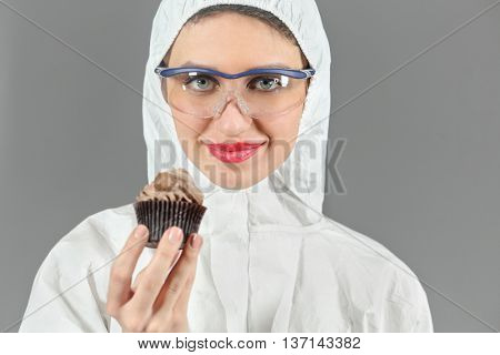Half-length portrait of woman holding  piece of tasty chocolate cake and looking at us, on gray background