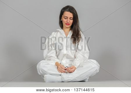 headshot of woman in white protective suit of synthetic paper, glasses and respiritory half mask, sitting in lotus position, looking down, on gray background