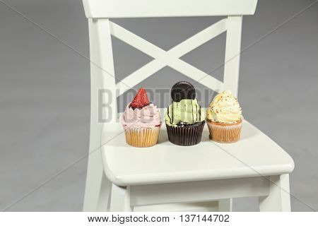 three cakes: with strawberries, cookies, whipped cream stand on white chair