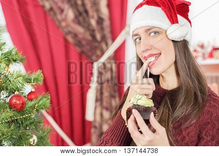 Half-length portrait of woman in burgundy sweater holding piece of tasty chocolate cake and try it for taste. Christmas interior with tree on background