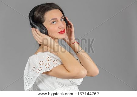 Half-length portrait of woman in white dress in headphones, listen music, looking at us, on gray background