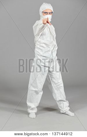 Half-growth portrait of woman in white protective suit of synthetic paper and respiritory half mask, looking at us, pointing at us