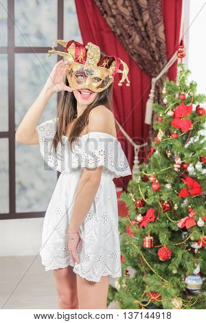 Full portrait of young woman in carnival mask jester standing near christmas three, look at us and smile. Christmas interior studio