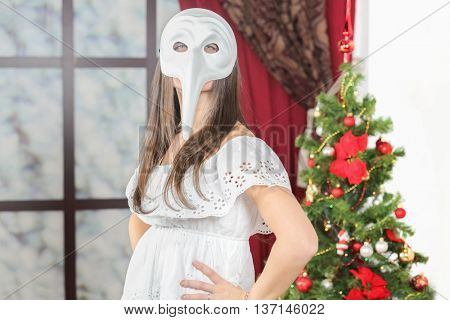 Half-length portrait of young woman in white mask with long nose standing near christmas three, look at us. Christmas interior studio