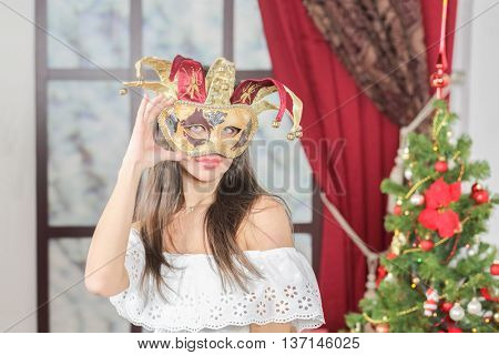 Half-length portrait of young woman in carnival mask jester standing near christmas three