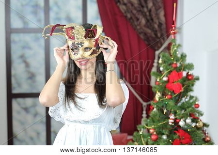 portrait of young woman in carnival mask jester standing near christmas three, looking away. Christmas interior studio