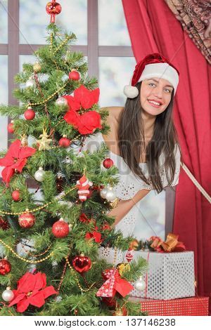 Portrait of woman near Christmas tree. Girl in white dress and Santa hat dresses up Christmas tree.