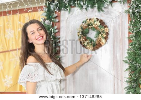 lovely woman with elegant style standing near door of house sham, knocking at door, look at us, close-up