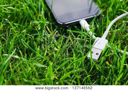 Phone detail with cable on grass ready to plug