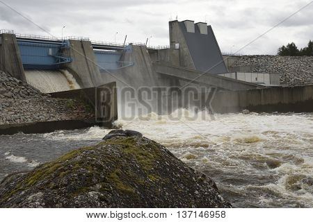 Water power plant with hatchway open and water flowing picture from the North of Sweden.