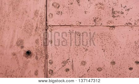 part of the gray rusty scratched metal gate covered with dark pink stains it is visually divided into three parts, a hole for a key