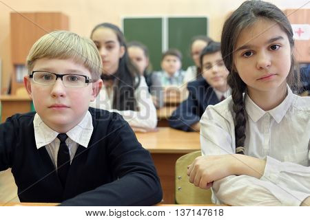seven students sitting at desk in classroom, shallow dof, focus on boy and girl in foreground