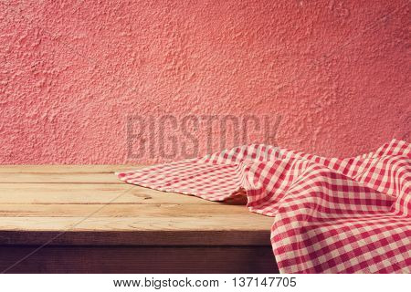 Empty wooden deck table with red checked tablecloth over red wall background