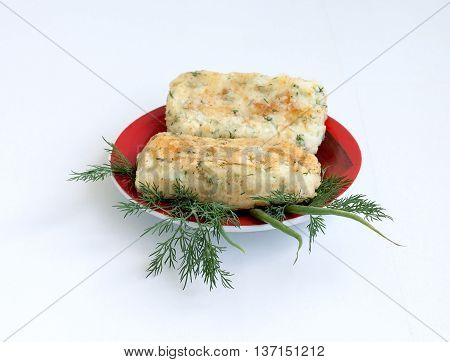 Cookery. Potatoes and cheese fried rolls with vegetables on a red plate
