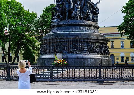 VELIKY NOVGOROD RUSSIA -JUNE 11 2016. Unidentified tourist girl takes the shot of the monument Millennium of Russia - famous bronze monument in the Novgorod Kremlin