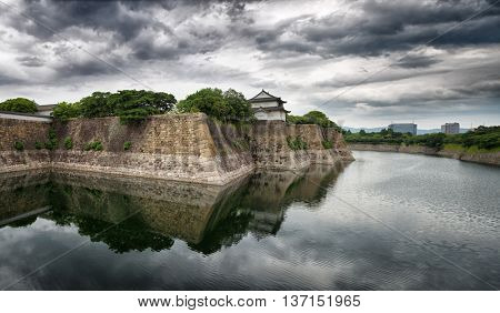 Panorama of Osaka Castle walls and moat. Dramatic skies with mirrored reflection.