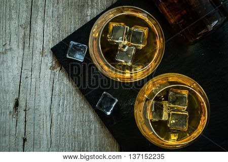 Cognac in glasses on rustic backgrpund, copy space