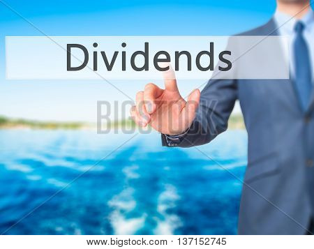 Dividends - Businessman Hand Pushing Button On Touch Screen