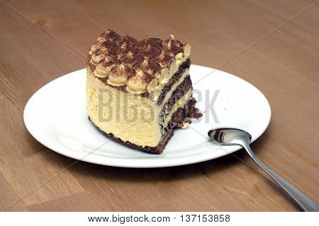 A piece of sponge cake on a white plate with a teaspoon on the wooden table surface. Horizontal photo closeup