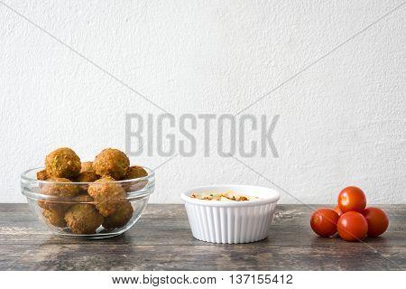 Falafels, lettuce, tomatoes and hummus on wood