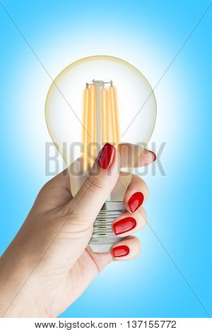 LED filament light bulb in female hand. Isolated on blue background.