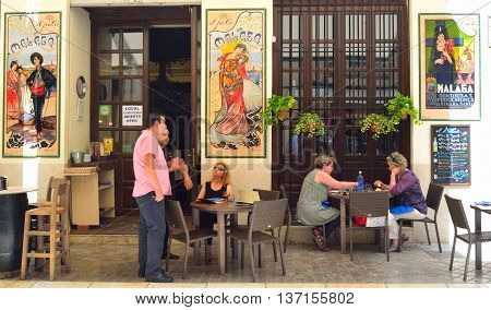 Malaga, Andalucia, Spain - June 29, 2016: Spainish tapas Bar with colourful ceramic tiles on walls, customers enjoying lunch.