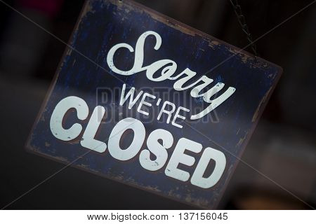 Close up of a vintage closed sign on a shop window