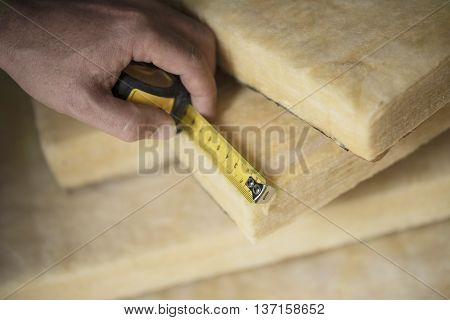 Hand measuring a fiberglass batt. Image of home insulation.
