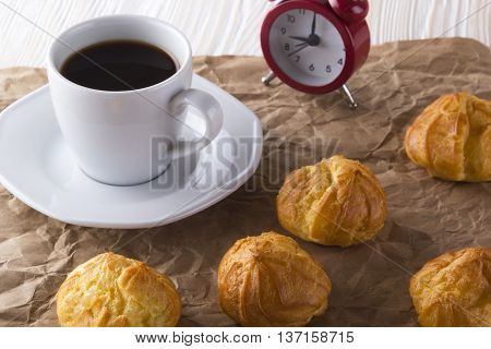 Eclair, coffee cup and alarm clock on wooden background.
