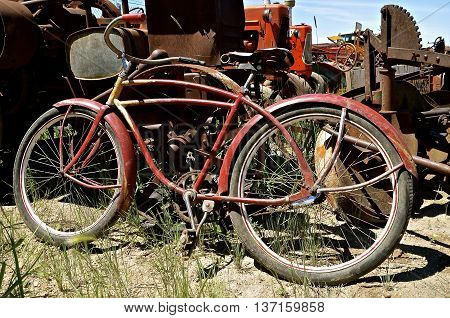 Old retro bike leans against old rusty tractor parts in a salvage junkyard