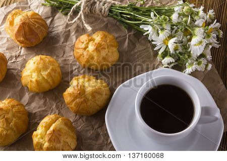 Eclair, coffee cup and charmomile on wooden background.