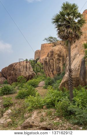 Chettinad India - October 16 2013: View from outside the Thirumayam fort on a corner of the fortifications. Boulders and trees in foreground.