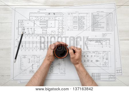 Close-up hands of man holding a cup of coffee over drawing layout in top view. Workplace of architect or constructor. Engineering work. Uplifting mood. Coffee break.
