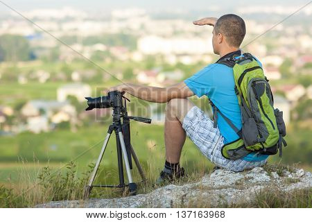 Hiker photographer sitting on a rock looking forward near a camera on a tripod