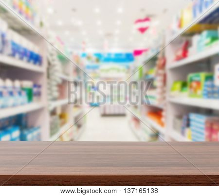 Wood table counter top on blurred shelves pharmacy store