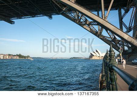 Sydney, Australia - January 26, 2011; Sydney opera House along harbor edge two people walking under silhouette structure of Sydney Harbor Bridge.