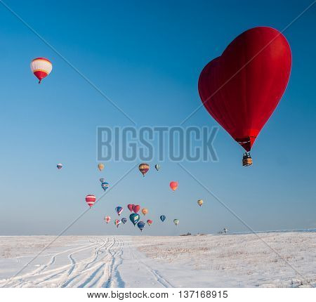 Balloon in the form of heart on snow field and the other colored balls away