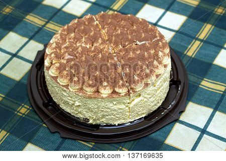 Round sponge cake on green checkered tablecloth on kitchen table. Top view closeup