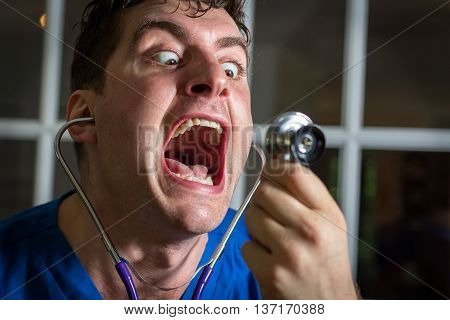 Crazy lunatic male nurse yells into his own stethoscope